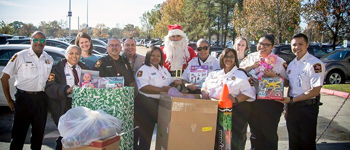 UT Police at Houston volunteers from last year's annual Children's Gift Drive deliver gifts to pediatric patients at the Lyndon B. Johnson Hospital Child Life Center.