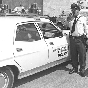 Archival photograph of UT Police officer calling in to dispatch center