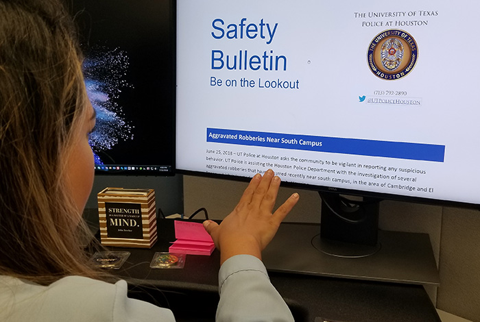 An employee reads a safety bulletin on her computer monitor.
