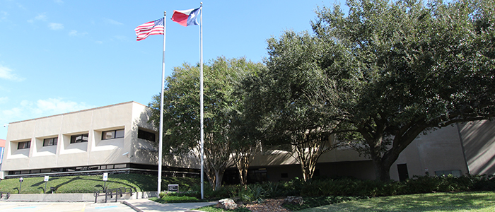U.S. and Texas flags fly at UT Police at Houston headquarters, 7777 Knight Road.